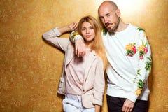 Façonnez le type avec une fille dans le studio posant sur un backgroun d'or Photos stock