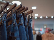 Façonnez les blues-jean sur le cintre en bois dans le magasin La mode vêtent photos libres de droits