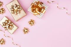 Façonnez les cadeaux ou présentez des boîtes avec les arcs d'or sur la vue supérieure de fond en pastel rose Configuration plate  photos stock