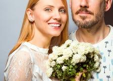 Façonnez les couples dans l'amour avec un bouquet blanc de couleur dans le goujon Image libre de droits