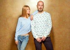 Façonnez les couples de hippie dans l'amour en verres posant sur un fond d'or Photographie stock