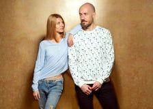 Façonnez les couples de hippie dans l'amour posant sur un fond d'or Images stock