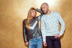 Façonnez les couples de hippie dans l'amour posant sur un fond d'or E Images stock