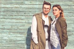 Façonnez les couples en verres avec des verres dans des vêtements verts posant o photographie stock libre de droits