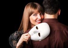 Façonnez les couples heureux dans l'amour se tenant avec le visage de masque Photographie stock libre de droits
