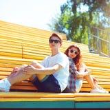 Façonnez les jeunes couples dans des lunettes de soleil se reposant sur le banc Photos stock