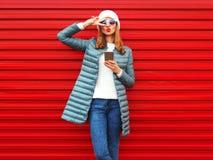 Façonnez les lèvres de soufflement de jolie femme, utilisant le smartphone sur un rouge Photographie stock libre de droits