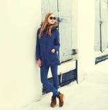 Façonnez les lunettes de soleil de port de veste de femme assez blonde dans la ville d'hiver Photographie stock libre de droits
