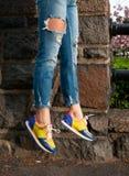 Façonnez les pieds du ` s de femme, les jeans de port et les espadrilles élégantes Photos libres de droits