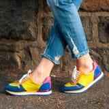 Façonnez les pieds du ` s de femme, les jeans de port et les espadrilles élégantes Images stock