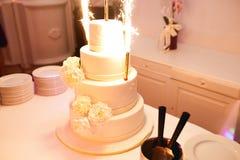 Faísca dos fogos de Bengal que está sendo posta em um bolo de casamento bonito fotos de stock royalty free