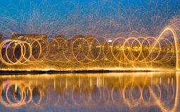 Faíscas douradas quentes que voam das palhas de aço ardentes de giro do homem Fotografia de Stock Royalty Free