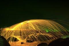 Faíscas douradas quentes que voam das palhas de aço ardentes de giro do homem em uma esfera em Rocky Shoreline Fotografia de Stock