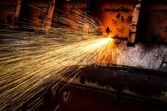 faíscas douradas quentes que voam do trabalhador a cortar o aço em um const Fotos de Stock Royalty Free