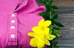 Fałdowe kobiety myli koszulkę z żółtymi florami dekorować na drewnianym tle Zdjęcia Stock