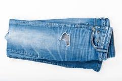 Fałdowi rozdzierający niebiescy dżinsy na białym tle Odgórny widok Moda Zdjęcia Royalty Free