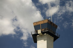 FAA Control Tower Cab. A horizontally aligned image of cumulus clouds floating behind a Federal Aviation Administration (FAA) control tower cab stock photo