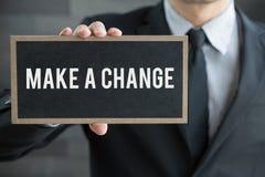 Faça uma mudança, a mensagem no quadro-negro e a posse pelo homem de negócios Imagens de Stock