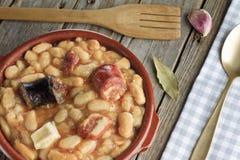 Fabada espagnol dans un plat de poterie de terre avec une fourchette en bois Photos stock