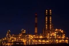 Fabbrica con le luci intense a produzione di petrolio di tramonto, del gas e Fotografia Stock Libera da Diritti