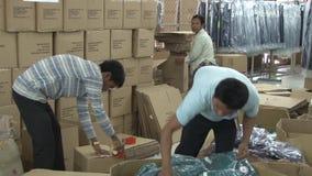 Fabbrica dell'indumento del tessuto: Due indumenti completati pacchetto maschio dei lavoratori in scatole video d archivio