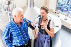 Fabbricante di birra e donna che tostano nella fabbrica di birra della birra Immagine Stock Libera da Diritti