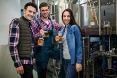 Fabbricanti di birra che tengono i vetri di birra alla fabbrica della fabbrica di birra Fotografia Stock Libera da Diritti