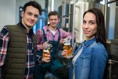 Fabbricanti di birra che tengono i vetri di birra alla fabbrica della fabbrica di birra Fotografia Stock