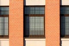 Fabbricato industriale con i pali arancio dei mattoni fra le finestre con protezione arrugginita delle barre di metallo fotografia stock libera da diritti