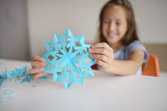 Fabbricazione dei fiocchi di neve dalla carta blu Immagini Stock Libere da Diritti