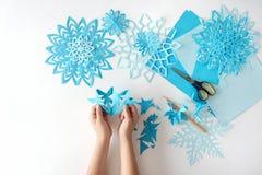 Fabbricazione dei fiocchi di neve dalla carta blu Immagine Stock Libera da Diritti