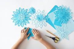 Fabbricazione dei fiocchi di neve dalla carta Progetto tradizionale di arti e dei mestieri di Natale Fotografia Stock Libera da Diritti