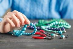 Fabbricazione dei gioielli fatti a mano Scatola con le perle ed i cuori di vetro su vecchio fondo di legno Accessori fatti a mano Fotografia Stock
