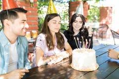 Fabbricazione del desiderio in Front Of Birthday Cake fotografia stock libera da diritti