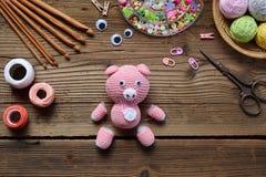 Fabbricazione del maiale rosa Lavori all'uncinetto il giocattolo per il bambino Sulla tavola infila, aghi, il gancio, filo di cot immagine stock libera da diritti