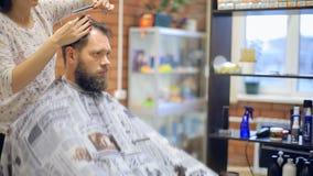 Fabbricazione del taglio di capelli uomo barbuto che ottiene taglio di capelli mentre sedendosi nella sedia al parrucchiere video d archivio