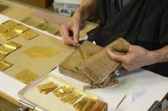 Fabbricazione della stagnola di oro Immagine Stock