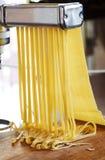Fabbricazione delle tagliatelle con una macchina della pasta Fotografie Stock Libere da Diritti