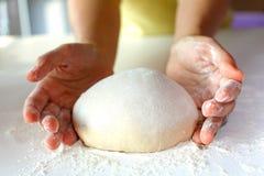 Fabbricazione di pane ed impastare sull'area lavoro impolverata fotografia stock