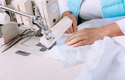 Fabbrichi il lavoro manuale delle mani della macchina per cucire del tessuto della cucitrice fotografie stock libere da diritti