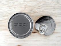 Fabbrichi la data e la data di scadenza stampate sul fondo delle latte di alluminio su fondo di legno fotografia stock