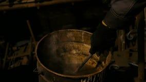 Fabbro che estigue la parte calda del ferro del portone forgiato stock footage