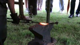 Fabbro che lavora al metallo sull'incudine alla forgia video d archivio
