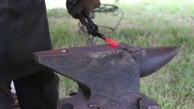 Fabbro che lavora al metallo sull'incudine alla forgia stock footage