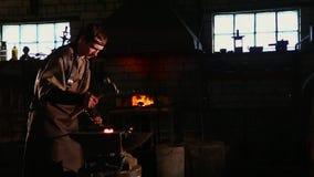 Fabbro che lavora nel metallo caldo della forgia stock footage