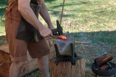 Fabbro Working Incandescent Iron con il martello e l'incudine Fotografia Stock Libera da Diritti