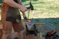 Fabbro Working Incandescent Iron con il martello e l'incudine Immagini Stock