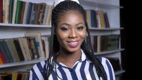 Fabelachtig Afrikaans meisje die zich nog en camera in bibliotheekrust bekijken en ontspannen bevinden stock footage