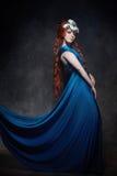 Fabelachtige roodharige het meisje kijkt, blauwe lange kleding, heldere make-up en grote wimpers Geheimzinnige feevrouw met rood  royalty-vrije stock fotografie