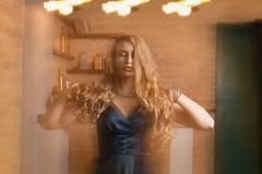 Fabelhafte Blondine im Kleid, das in Mischlicht am Studio aufwirft Lizenzfreies Stockfoto